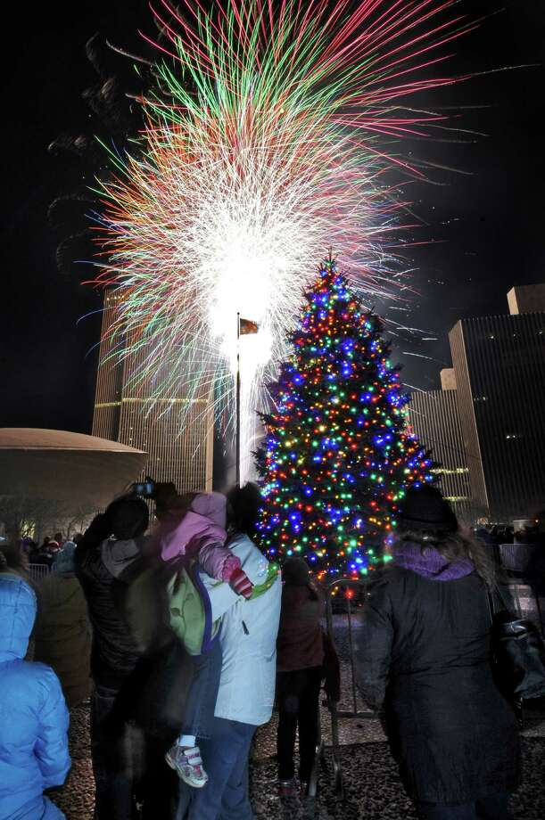Robin Maynard of Cohoes holds her daughter Lindsey, 2, while watching the annual Christmas tree lighting ceremony and fireworks at the Empire State Plaza on Sunday evening Dec. 4, 2011 in Albany, NY. (Philip Kamrass / Times Union ) Photo: Philip Kamrass / 00015663A