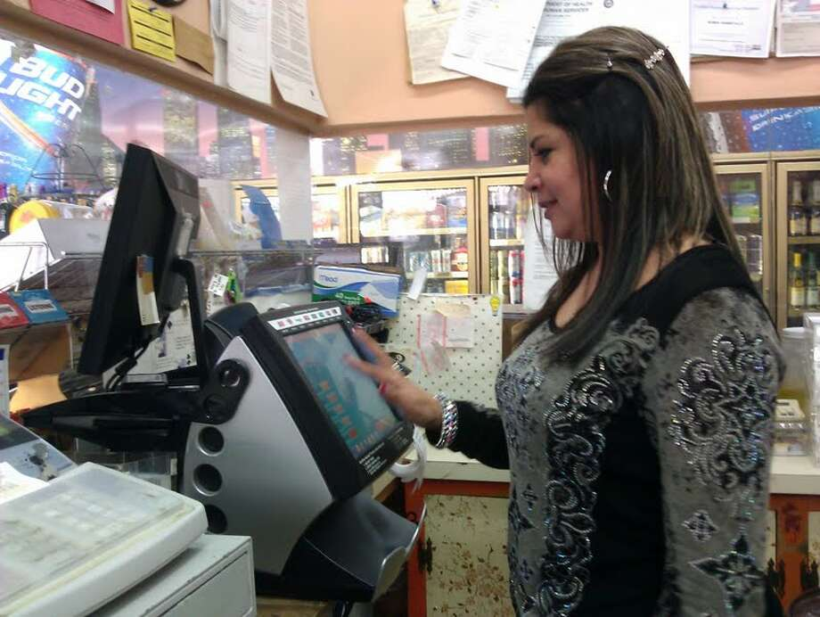 Dolores Rangel, manager at Gray Stop 'N Shop, says the neighborhood store does a brisk trade in Powerball tickets. Photo: Carol Christian / Chronicle