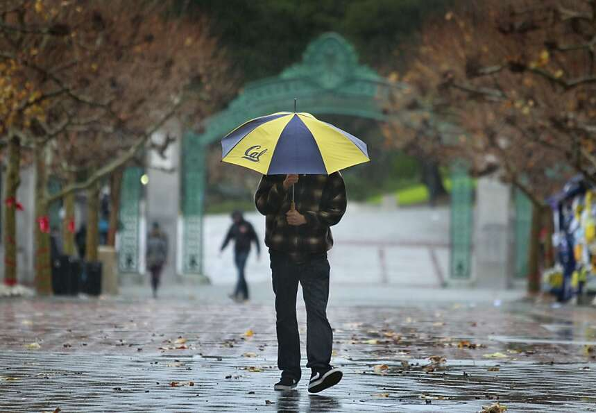 A student walks in the rain on Sproul Plaza at UC Berkeley on Wednesday, Nov. 28, 2012.