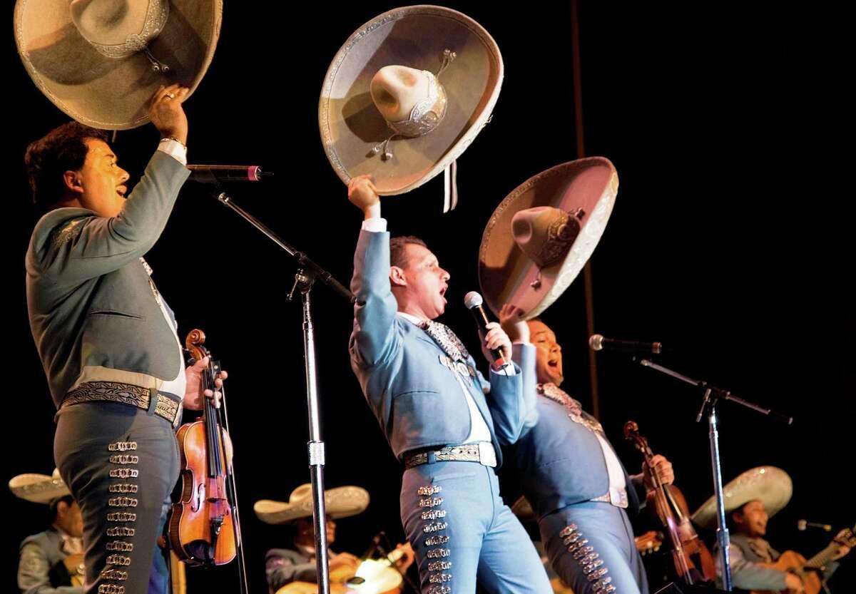 Members of Mariachi Vargas de Tecalitlan wave their sombreros during a performance