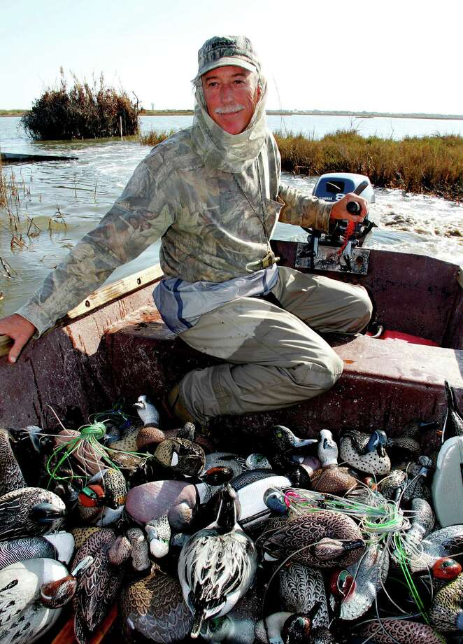 Ed Duvall, second-generation member of the century-old Port Bay Hunting and Fishing Club, maneuvers one of the club's locally-made skiffs through a tract of marsh the club purchased  to prevent it from being lost to development. Photo: Picasa, Shannon Tompkins/Chronicle