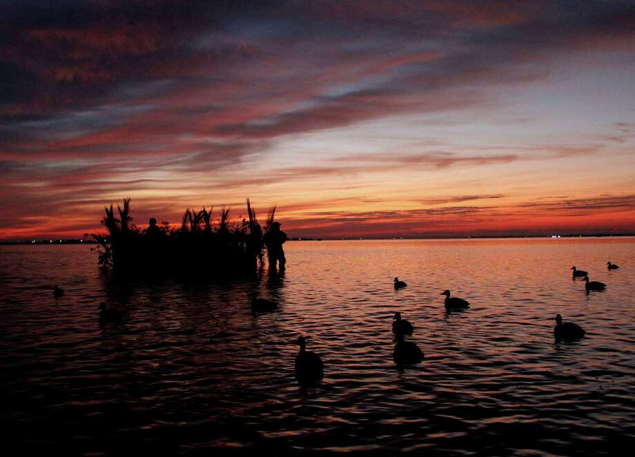 Today's waterfowling members of the Port Bay Hunting and Fishing Club, the oldest continously-operated private hunting/fishing club on the Texas coast, await dawn in club-built duck blinds, many of which have been in the same locations since the club began in 1912.  Photo: Picasa, Shannon Tompkins/Chronicle
