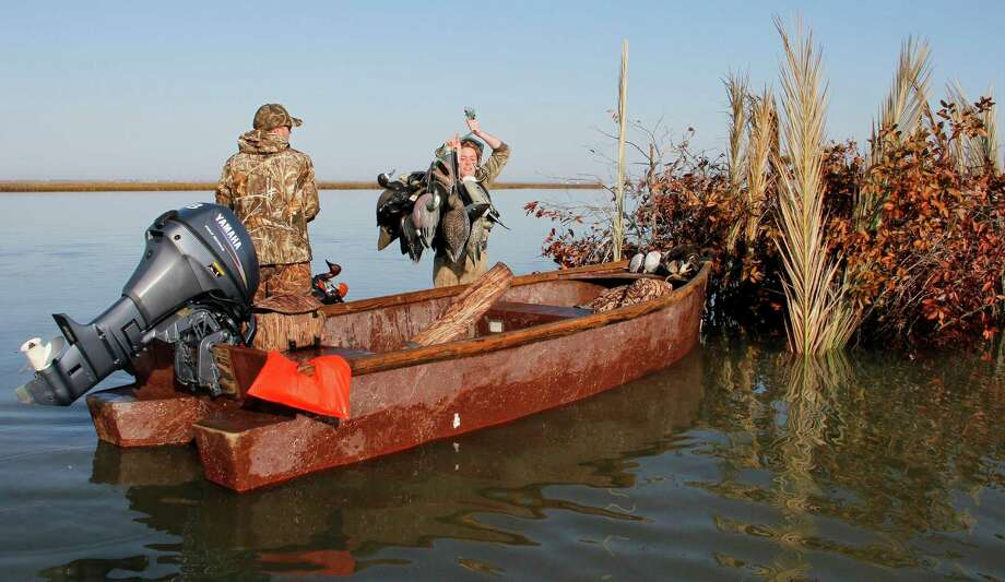 After a successful morning duck hunt on a shoalgrass-covered flat , Brian Smith and Rebecca Duvall lift decoys into a Port Bay Club skiff. The fiberglass skiffs, which fit inside the adjacent duck blind, were built from a mold taken of the wooden skiffs the century-old mid-coast hunting/fishing club used for decades. Photo: Picasa, Shannon Tompkins/Chronicle