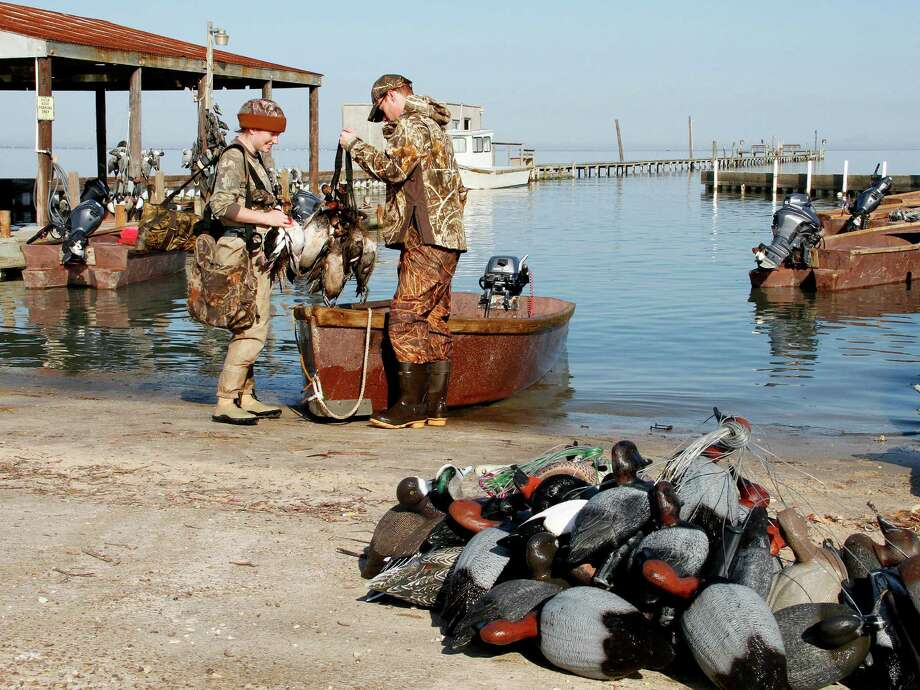 Rebecca Duvall and Brian Smith unload gear and ducks from a skiff at the dock of the century-old  Port Bay Hunting and Fishing Club near Rockport. Photo: Picasa, Shannon Tompkins/Chronicle