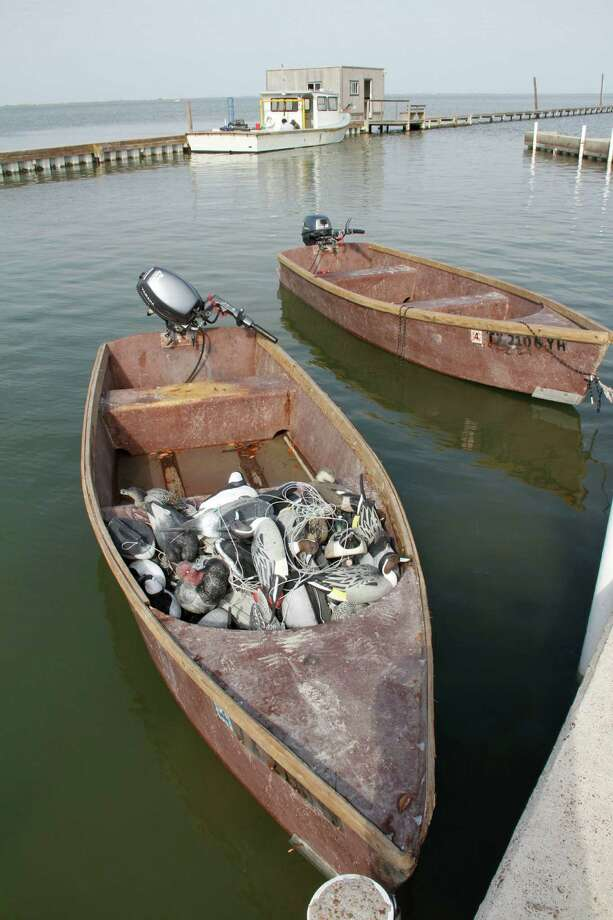 A pair of Port Bay Club skiffs, built of fiberglass using a mold made from one of the club's old wooden skiffs, wait at the club's dock for their next hunt. The motor launch used to tow the boats to hunting locations floats in the background.  Photo: Shannon Tompkins/Chronicle