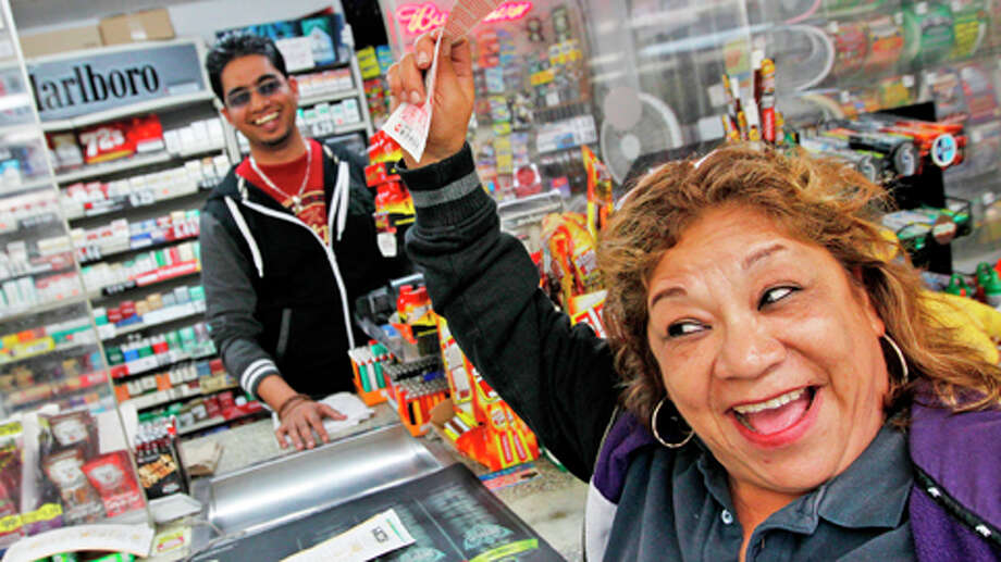 Raising her Power Ball ticket in the air Hortcina Martinez, who plays power ball weekly, shouts in excitement in hopes of winning jackpot from a ticket purchased at Oscar's Food Mart #1 on Tuesday, Nov. 27, 2012, in Houston. Photo: Mayra Beltran, . / Houston Chronicle