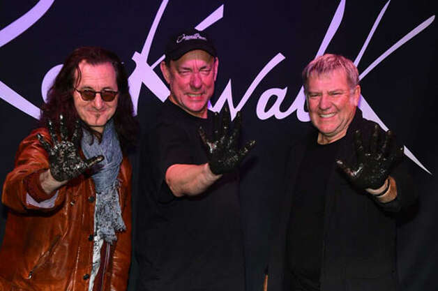 Rush members (from left) Geddy Lee, Neil Peart and Alex Lifeson were honored on Guitar Center's RockWalk this month in Hollywood. Getty Images