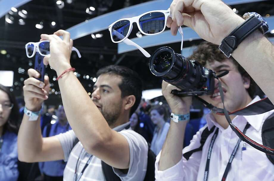 Visitors to the Volkswagen Beetle convertible  world debut photograph thorough polarized lanes at the LA Auto Show in Los Angeles, Wednesday, Nov. 28, 2012. Photo: Chris Carlson, Associated Press