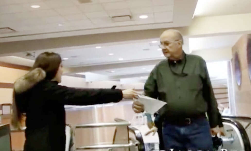 Ashley Jessica, left, is stopped by Albany International Airport Director of Public Affairs Doug Myers, right, after handing out information concerning travelers' rights to opt out of the full-body scanner used at the security checkpoint and to film any patdown by TSA officials. (YouTube)