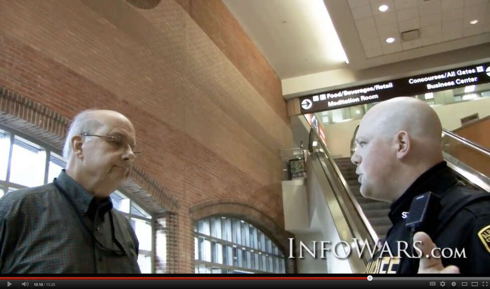 Albany International Airport Airport Director of Public Affairs Doug Myers, left, and Deputy Sheriff Stan Lenic, right, discuss what to do with activists, Ashley Jessica and cameraman Jason Bermas who were handing out information concerning travelers' rights to opt out of the full-body scanner used at the security checkpoint and to film any patdown by TSA officials. (YouTube)