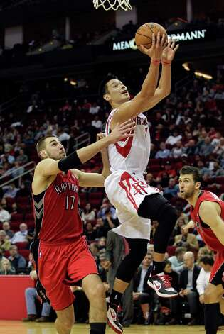Houston Rockets'  Jeremy Lin (7) drives to the basket past Toronto Raptors' Jonas Valanciunas (17 ) for a layup in the second half of an NBA basketball game Tuesday, Nov. 27, 2012, in Houston. Houston won 117-101. (AP Photo/Bob Levey) Photo: Bob Levey, FRE / FR156786 AP