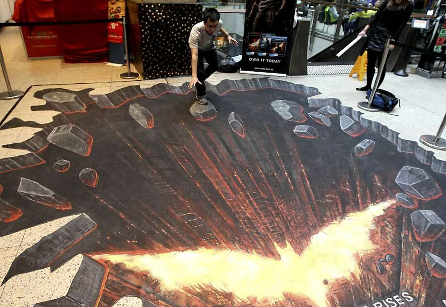 "To the Bat Hole, Robin! A young man pretends to stand on a rock breaking off of a ledge in a 3-D chalk-art drawing of a scene from ""The Dark Knight Rises,"" showing at a shopping mall in Sydney. Photo: Rob Griffith, Associated Press"