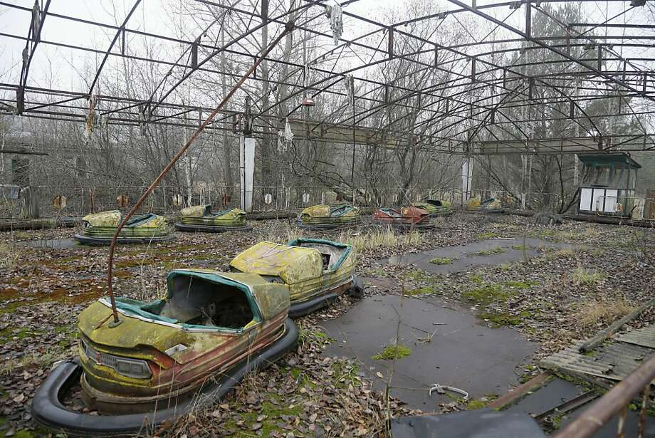 Welcome to Radioactive Land! Bumper cars at an old amusement park in Pripyat, Ukraine, haven't collided with each other since April 26, 1986, when a series of explosions at a reactor of the Chernobyl power station three kilometers away caused the worst nuclear plant disaster in history. Workers raised the first section of a colossal arch-shaped structure that will eventually cover the remnants of the reactor. Photo: Efrem Lukatsky, Associated Press