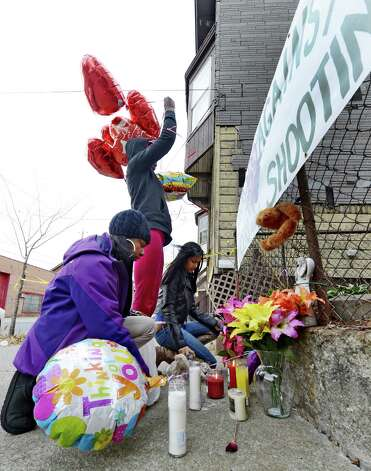 Sahasza Williams, foreground, Nierra Carter, center and Esther Degannes, background decorate a memorial to their friend and family member Tonette Thomas next to 157 Myrtle Street in Albany, N.Y. Nov. 28, 2012. Tonette Thomas was murdered here on Monday afternoon.  (Skip Dickstein/Times Union) Photo: SKIP DICKSTEIN
