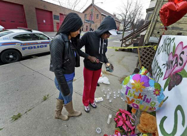Esther Degannes, left with Nierra Carter decorate a memorial to their friend and family member Tonette Thomas next to 157 Myrtle Ave. in Albany. Tonette Thomas was murdered here on Monday afternoon.  Degannes said Tonette was her best friend and Carter is Thomas' cousin.  (Skip Dickstein/Times Union) Photo: SKIP DICKSTEIN
