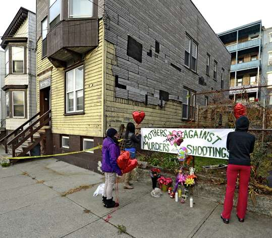 Sahasza Williams, center, Nierra Carter, right and Esther Degannes, left decorate a memorial to their friend and family member Tonette Thomas next to 157 Myrtle Street in Albany, N.Y. Nov. 28, 2012. Tonette Thomas was murdered here on Monday afternoon.  (Skip Dickstein/Times Union) Photo: SKIP DICKSTEIN