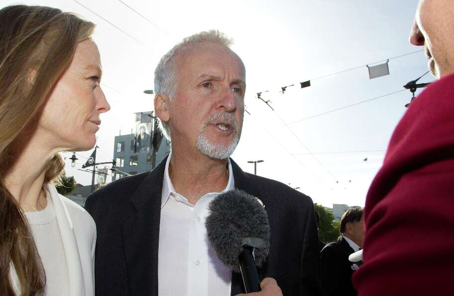 Director James Cameron (C) and Suzy Amis (L) speak to the media upon their arrival at the world prem