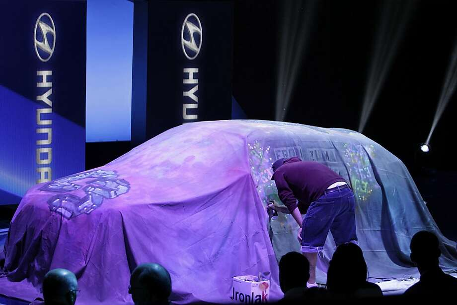 An artist spray paints the cover laying on top of the Hyundai Motor Co. Santa Fe during the LA Auto Show in Los Angeles, California, U.S., on Wednesday, Nov. 28, 2012. The LA Auto Show is open to the public Nov. 30 through Dec. 9. Photo: Jonathan Alcorn, Bloomberg