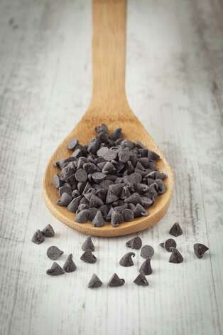 Small dark chocolate chips on a wooden spoon / sabino.parente - Fotolia