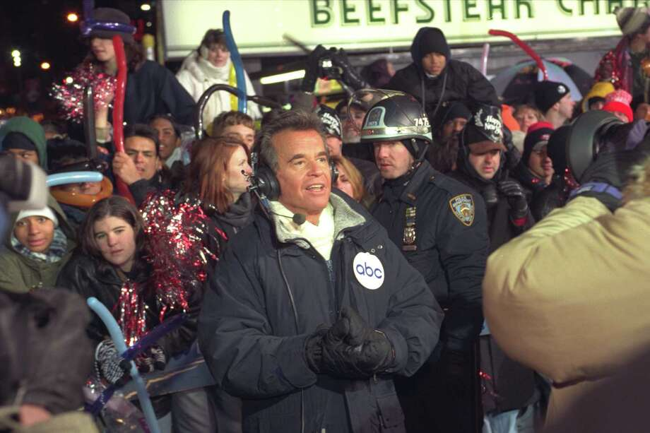"FILE - In this Dec. 31, 1996 file photo, Dick Clark broadcasts during New Year's festivities from Times Square in  New York.  ABC is turning its first New Year's Eve without Dick Clark in four decades partly into a celebration of the show biz impresario's life. Clark, who originated the annual ""New Year's Rockin' Eve"" special in 1971, died at age 82 in April 18, 2012. Fergie and Jenny McCarthy will be hosts of a two-hour tribute to Clark that will air at 8 p.m. ET on New Year's Eve. ABC said Wednesday, Nov. 28, 2012,  that Ryan Seacrest will host the countdown show from Times Square, with Taylor Swift, Carly Rae Jepsen, Neon Trees, Flo Rida and Pitbull among the musical guests. (AP Photo/Wally Santana) Photo: WALLY SANTANA"