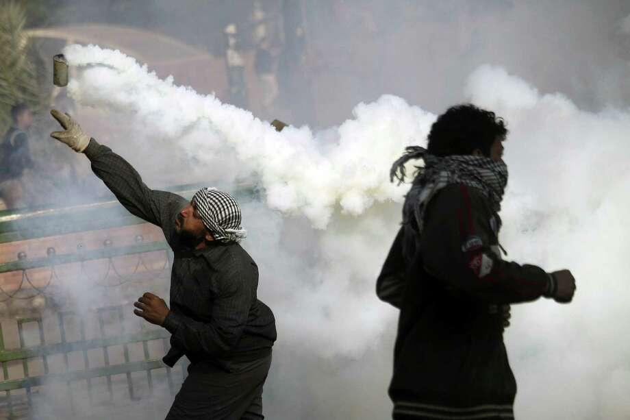 TOPSHOTS A protester throws back a tear gas canister during clashes with Egyptian riot Police on Tahrir Square on November 28, 2012 in Cairo. Police fired tear gas into Cairo's Tahrir Square, where several hundred protesters spent the night after a mass rally to denounce President Mohamed Morsi's assumption of expanded powers.       AFP PHOTO / MAHMOUD KHALEDMAHMOUD kHALED/AFP/Getty Images Photo: MAHMOUD KHALED, AFP/Getty Images / AFP