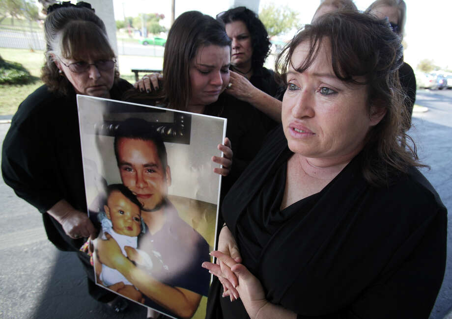 At the funeral for Ryan Yearly, Marilyn Yearley-Perez shows a photo of her son holding his infant child. Photo: Bob Owen, San Antonio Express-News / © 2012 San Antonio Express-News