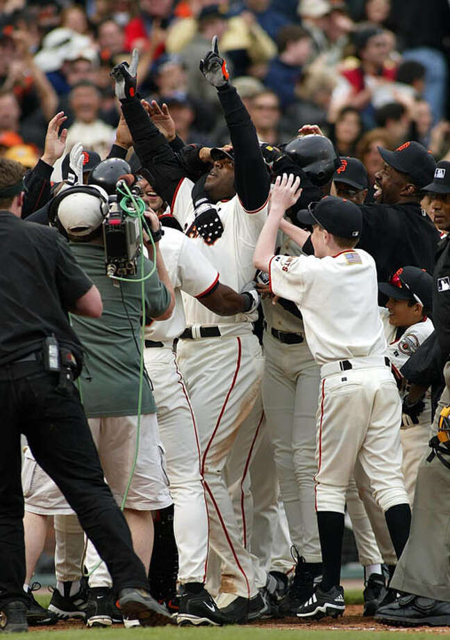 San Francisco Giants' slugger Barry Bonds (center) is mobbed by teammates after hitting the game-winning two-run home run in the 10th inning against the San Diego Padres 05 April 2002 in San Francisco. It was Bonds' 572 career home run as the Giants defeated the Padres 3-1. Photo: JOHN G. MABANGLO, AFP/Getty Images / AFP