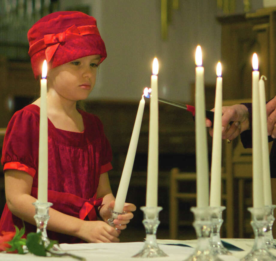 "A young friend teams with registered nurse Linda Lewis to light candles for the ""Time of Remembrance,"" a reading of names by Kathy Leier, R.N., Robert O'Keefe, LCSW, and Mary Peitler, M.A., during New Milford VNA Hospice's annual interfaith remembrance service at St. John's Episcopal Church. Nov. 18, 2012 Photo: Trish Haldin"