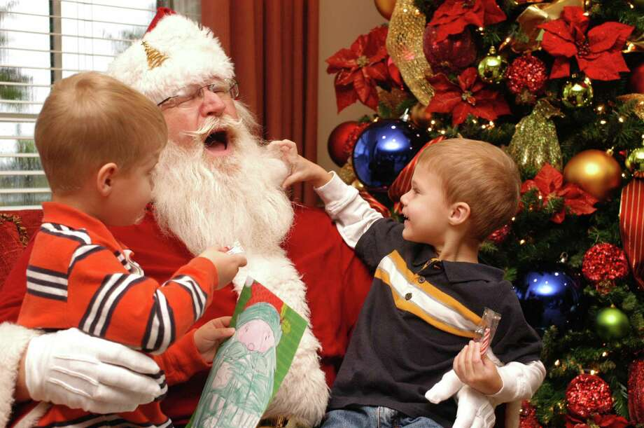 Bridgeland and The Woodlands are partnering for a holiday promotion Nov. 1 through Dec. 31 that offers a $2,000 gift card to those purchasing a new home in either community. Pictured are Zach Taylor, left, and brother Luke talking with Santa during a past holiday event in Bridgeland.
