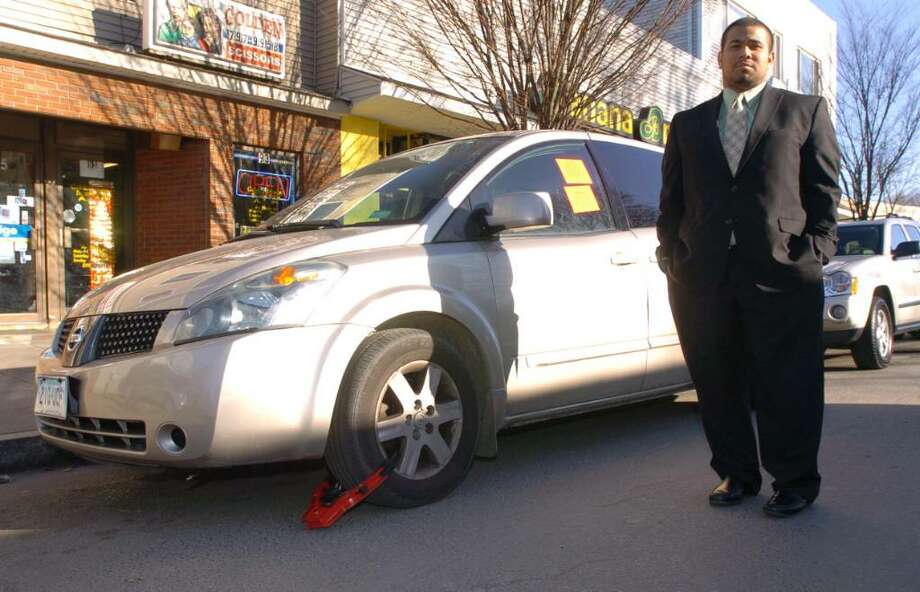 David Solis, of Danbury, stands on Main St next to his mothers car, wich was booted late last night. Image taken, Thursday, Dec. 17, 2009. Photo: Chris Ware / The News-Times