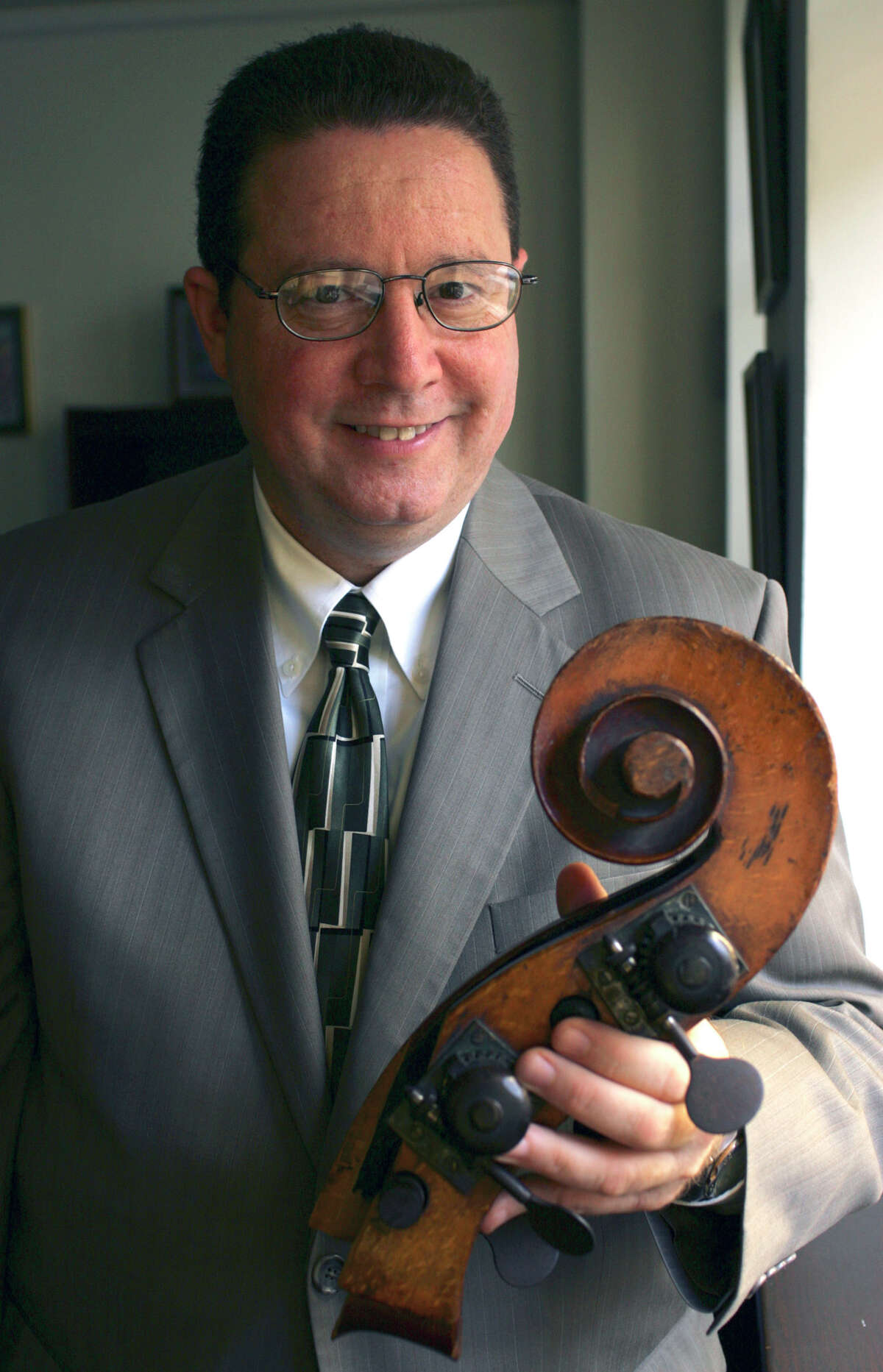 Jack Fishman, President and CEO of the San Antonio Symphony, holds the head of his double bass that broke off after an airline worker dropped the instrument years ago. He has since had the bass repaired. Friday, Nov. 14, 2008.