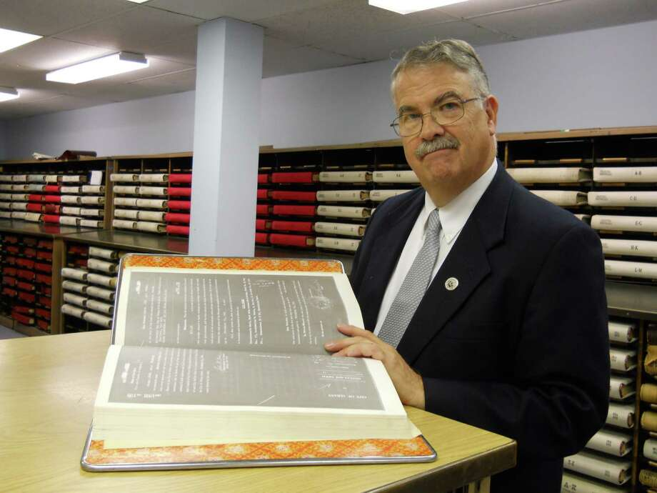 Albany County Clerk Tom Clingan leafs through one of the bound books containing images of older deeds recorded in the county.  Images of many newer deeds are recorded electronically and can easily be accessed with a computer, he said. Clingan is warning homeowners about mail solicitations urging them to pay $59.50 for certified copies of their deeds. In fact, the same document is available directly from the clerk's office for about $5, he said.(Cathy Woodruff / Times Union )