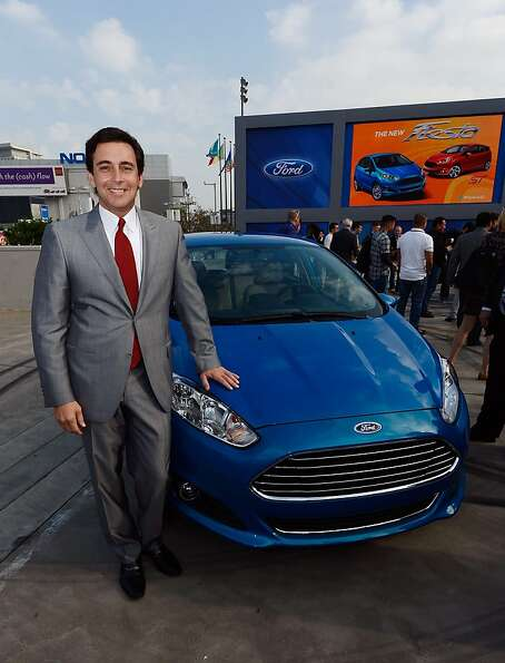 Mark Fields, chief operating officer of Ford Motor Company, stands next to the new Ford three-cylind