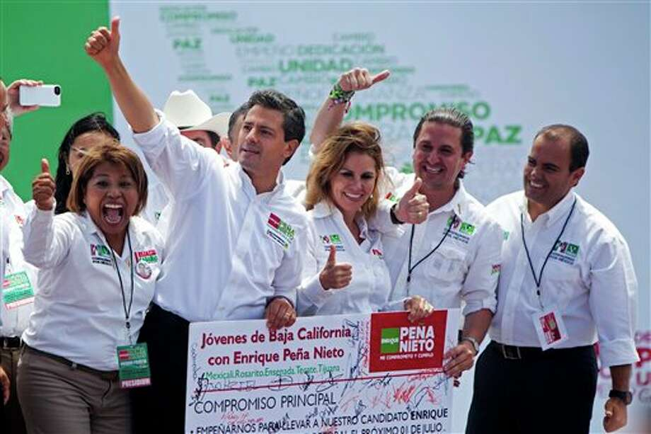 Mexican presidential candidate Enrique Pena Nieto of the Revolutionary Institutional Party (PRI), second from left, gestures to supporters while standing with unidentified Baja California state party members during a  campaign stop in the northern border city of Tijuana, Mexico, Sunday, June 3, 2012. On July 1, Mexico will hold presidential elections. (AP Photo/Alex Cossio) Photo: Alex Cossio, AP / AP