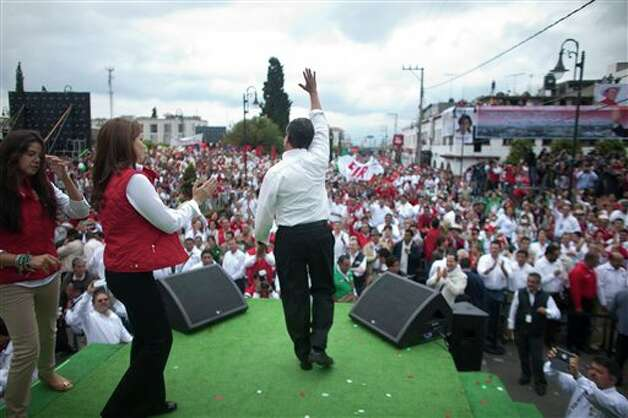 Presidential candidate Enrique Pena Nieto, of the Institutional Revolutionary Party, center, waves to supporters during a campaign rally in Atlacomulco, Mexico, Sunday, June 17, 2012. Mexico will hold presidential elections on July 1. (AP Photo/Alexandre Meneghini) Photo: Alexandre Meneghini, AP / AP