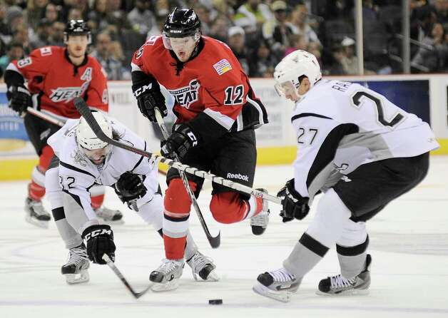 Abbotsford Heat's Paul Byron (12) skates between San Antonio Rampage's Greg Rallo, right, and Scott Timmins during an AHL hockey game, Saturday, Nov. 24, 2012, in San Antonio. (Darren Abate/pressphotointl.com) Photo: Darren Abate, PPI / Darren Abate/pressphotointl.com