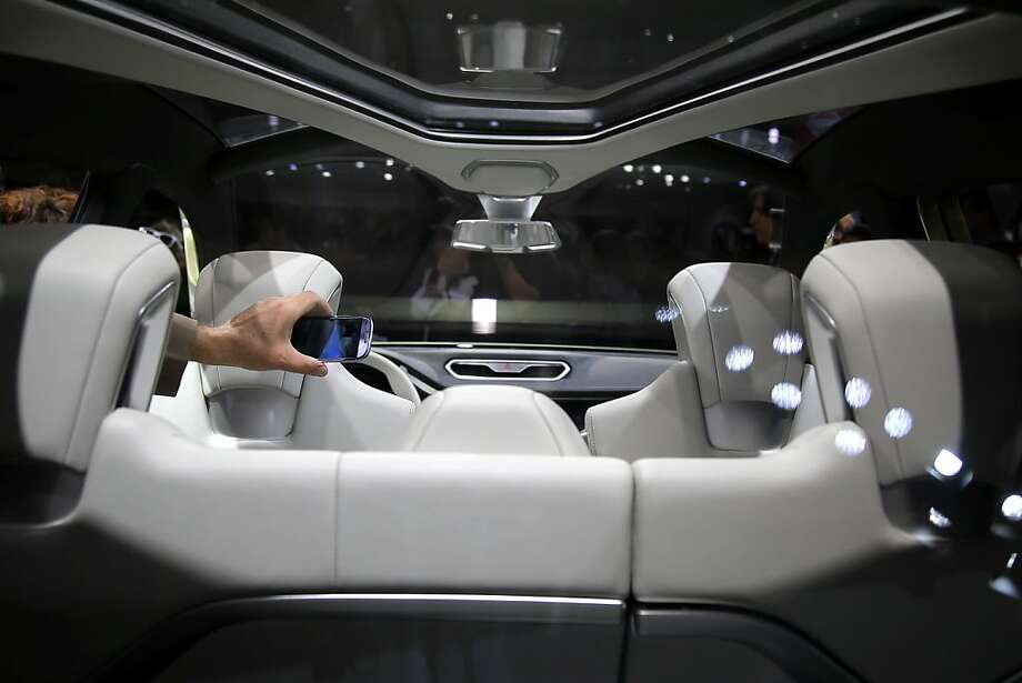 A show attendee uses his smartphone to photograph the interior of the Nissan Hi-Cross hybrid concept at the LA Auto Show in Los Angeles, Wednesday, Nov. 28, 2012. Photo: Jae C. Hong, Associated Press