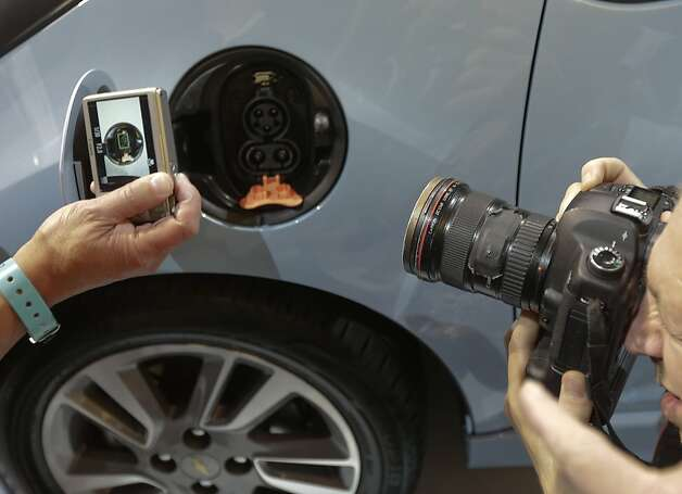 Members of the media photograph the charging port on the Chevy Spark EV during it's world debut at the LA Auto Show in Los Angeles, Wednesday, Nov. 28, 2012. (AP Photo/Chris Carlson) Photo: Chris Carlson, Associated Press