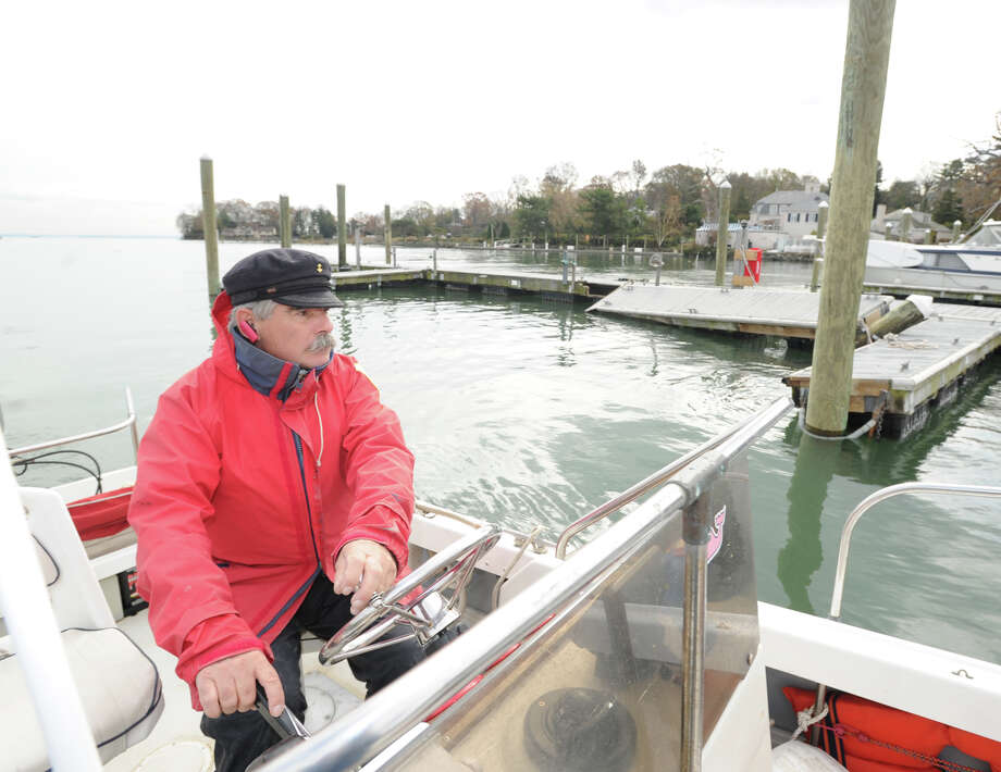 Aboard the town-owned Boston Whaler, Greenwich Harbor Master Ian MacMillan views the destruction caused by Hurricane Sandy in Greenwich Harbor Nov. 1, 2012 Photo: Bob Luckey / Greenwich Time
