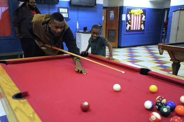 "Travon Davis, 8, plays a game of billiards with Stephen Jackson of the San Antonio Spurs at the Eastside Branch of the Boys & Girls Club on Wednesday, Nov. 28, 2012. Jackson and teammate Kawhi Leonard visited with children at the club. ""I want to ask him if he can dunk,"" Travon said. Photo: Billy Calzada, San Antonio Express-News / SAN ANTONIO EXPRESS-NEWS"