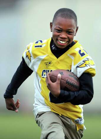 The Bridgeport Chargers United Youth Football team won the New England Regional Championship and are heading to the nationals in Florida.  Player Nazjhir Curry carries the ball as they run plays Wednesday, Nov. 28, 2012 at Went Field Park in Bridgeport, Conn. Photo: Autumn Driscoll / Connecticut Post
