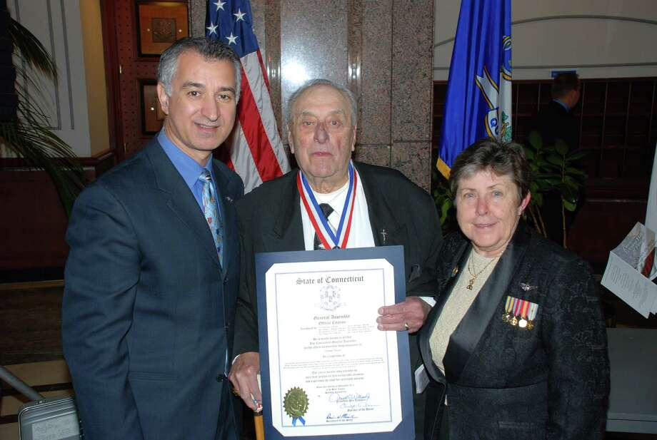 State Sen. Carlo Leone presents a citation to U.S. Navy veteran Carmine Vaccaro of Stamford along with state Veterans Commissioner Linda Schwartz during an induction ceremony to the Connecticut Veterans Hall of Fame at the capitol in Hartford. Photo: Contributed Photo