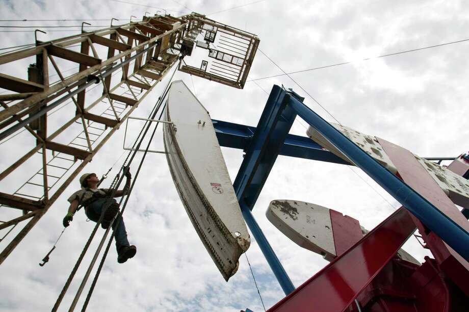 Ben Shaw hangs from an oil derrick near Williston, N.D. Investment in upstream spending is at a record high this year, often in places like North Dakota, but a study expects that to slow down in the coming years. Photo: Gregory Bull, STF / AP