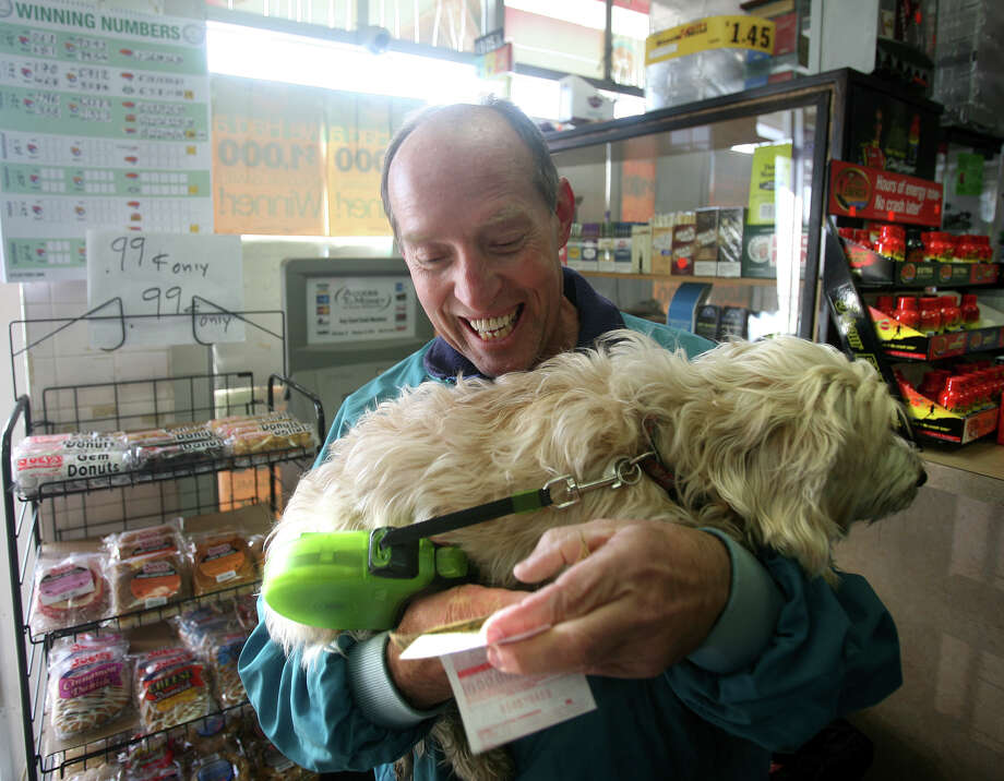 Mark Girard of Fairfield checks out his Powerball numbers as he carries his dog Jet in his arms at News Express at 200 Tunxis Hill Road in Fairfield on Wednesday, November, 28, 2012. Photo: Brian A. Pounds / Connecticut Post