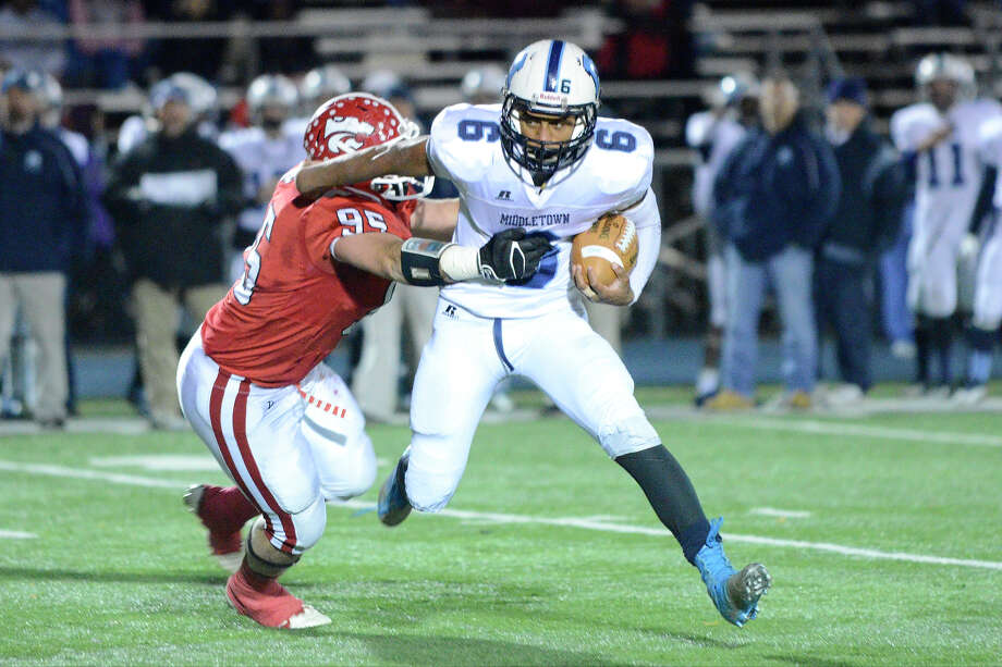 Masuk's defender Bryan Monaco goes for the tackle versus Middletown's Dario Highsmith as Masuk High School challenges Middletown High School in the Class L state varsity football quarterfinal game at Bunnell High School in Stratford, CT on Nov. 28, 2012. Photo: Shelley Cryan / Shelley Cryan for the CT Post/ freelance Shelley Cryan