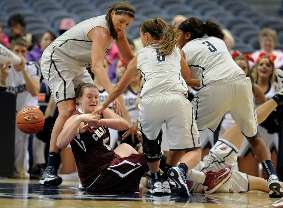 Colgate's Lulu Brase bottom looses the ball when pressured by Connecticut's Stefanie Dolson, top left, Caroline Doty (5), Morgan Tuck (3), and Kelly Faris, behind, during the first half of a NCAA college basketball game in Hartford, Conn., Wednesday, Nov. 28, 2012. (AP Photo/Jessica Hill) Photo: Jessica Hill, Associated Press / FR125654 AP