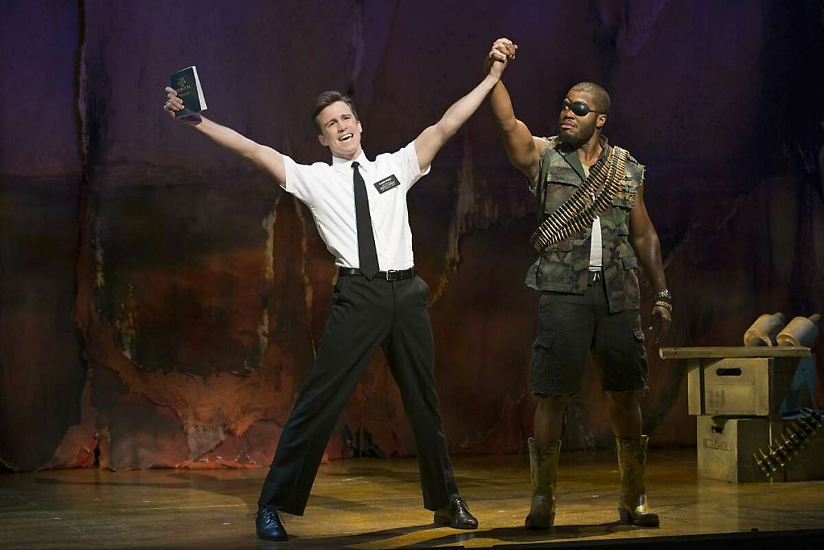 """Elder Price (Gavin Creel, left) spreads the word to the General (Derrick Williams) in Uganda in the national tour of """"The Book of Mormon"""" Book of Mormon"""