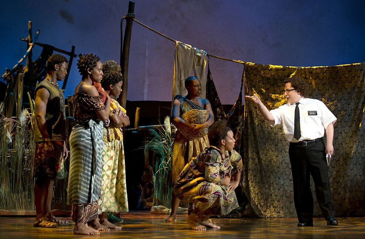 """Elder Cunningham (Jared Gertner, right) meets Ugandan villagers in the national tour of """"The Book of Mormon"""" Book of Mormon Tour"""