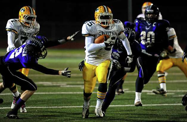 Trinity Catholic's #35 Sean Brown evades two North Branford players on his way to the endzone for a touchdown, during CIAC Class S boys football quarterfinal action in Guilford, Conn. on Wednesday November 28, 2012. Photo: Christian Abraham / Connecticut Post