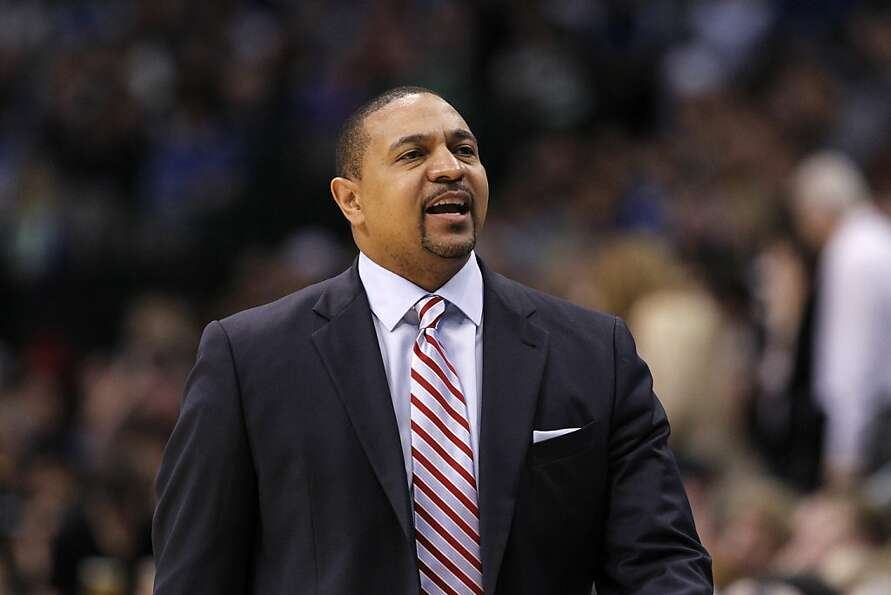 Golden State Warriors head coach Mark Jackson talks to a staff member during an NBA basketball game